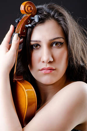 Female violin player against background photo