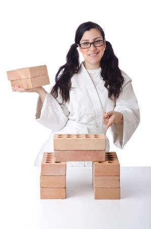 Woman karate breaking bricks on white photo