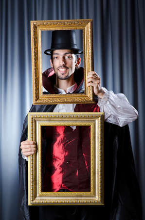 conjuror: Magician with photoframe in studio