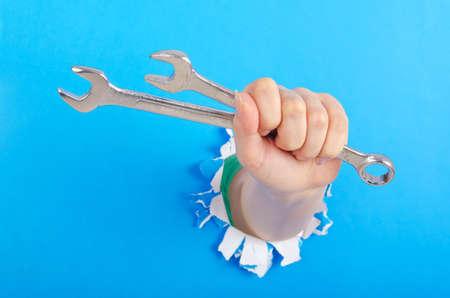 tabassum: Hand holding chrome wrenh