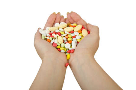 Hands holding pills on white photo