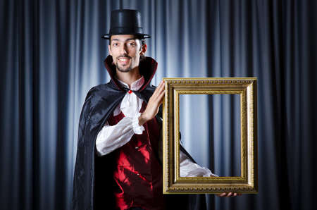 Magician with photoframe in studio Stock Photo - 15300538