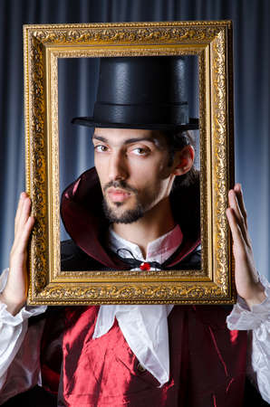 Magician with photoframe in studio Stock Photo - 15301428