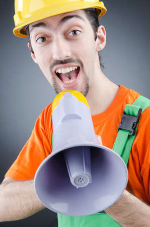 Construction worker with loudspeaker in studio photo