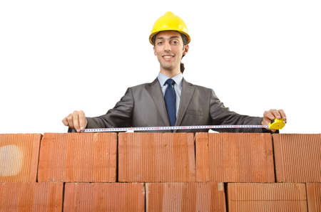 Businessman with bricks on white photo