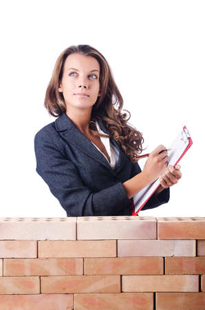 Woman builder and brick wall photo
