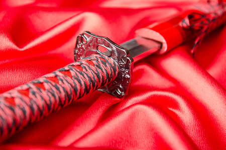 Japanese sword takana on red satin background photo