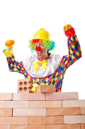 Bad construction concept with clown laying bricks photo