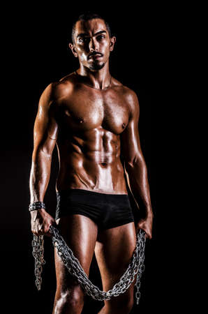 Bodybuilder with chains in dark photo