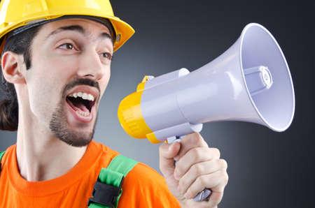 Construction worker with loudspeaker in studio photo
