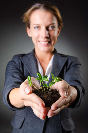 Businesswoman with seedlings and coins Stock Photo - 15441547