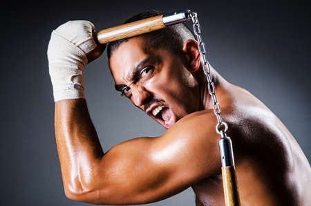 Strong man with nunchaku photo