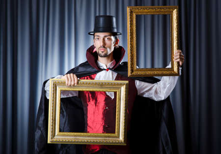 Magician with photoframe in studio Stock Photo - 15567450