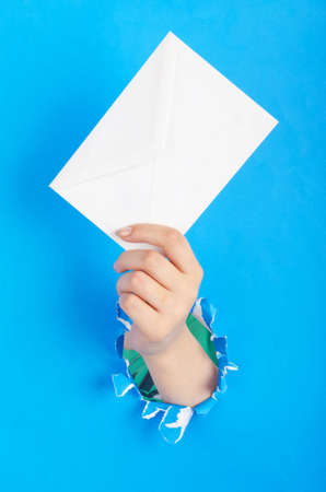 Hand holding paper envelope from hole photo