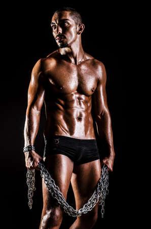 Bodybuilder with chains in dark Stock Photo - 15570861