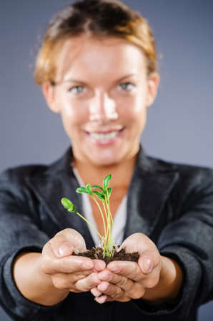 Businesswoman with seedlings and coins Stock Photo - 15570873