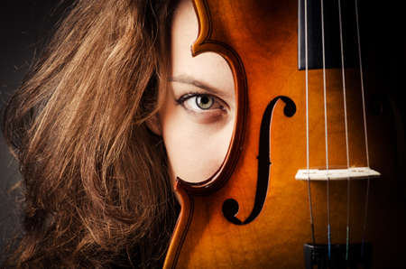 fiddles: Woman with violin in dark room Stock Photo