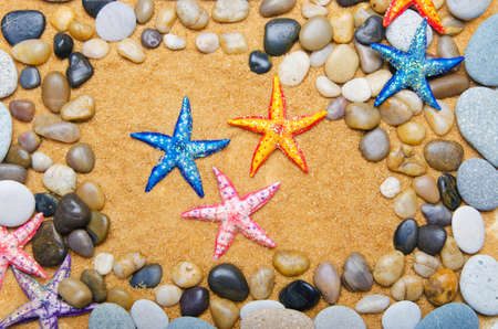 Sea stars and pebbles on sand photo