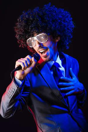 karaoke singer: Young singer in afro wig singing at disco