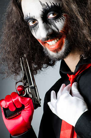 Evil clown with gun in dark room photo
