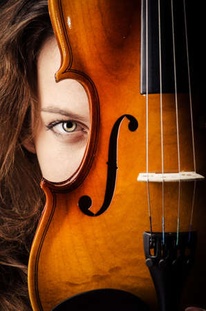 violas: Woman with violin in dark room Stock Photo