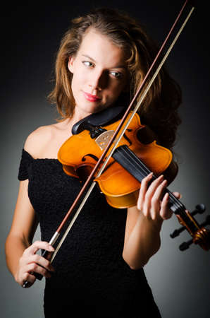 solo violinist: Woman with violin in dark room Stock Photo