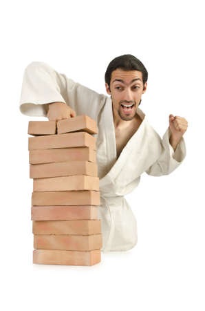 Karate man breaking bricks on white photo