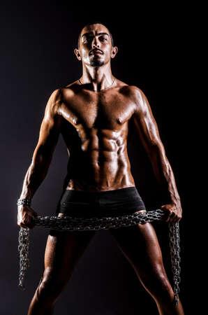 muscled: Bodybuilder with chains in dark