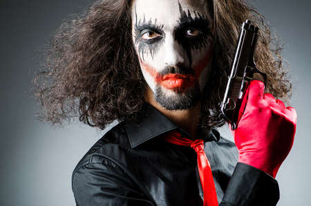harlequin clown in disguise: Evil clown with gun in dark room Stock Photo