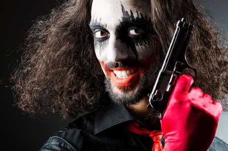 gun room: Evil clown with gun in dark room Stock Photo