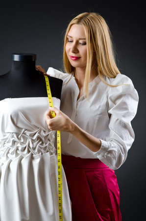 designer clothes: Woman tailor working on dress