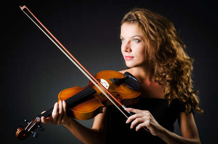 classical music: Woman with violin in dark room Stock Photo