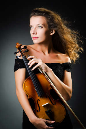 Woman with violin in dark room photo