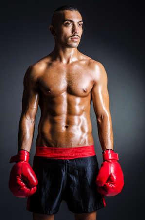 boxeadora: Boxeador con los guantes rojos en cuarto oscuro Foto de archivo
