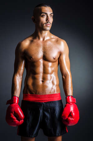 male boxer: Boxer with red gloves in dark room