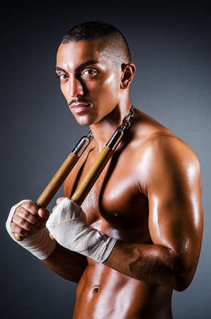 Strong man with nunchaku Stock Photo - 16483113