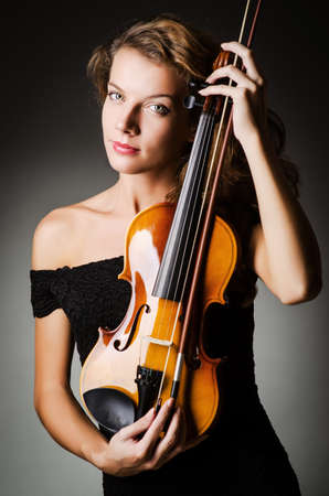 Woman performer with violin in studio photo