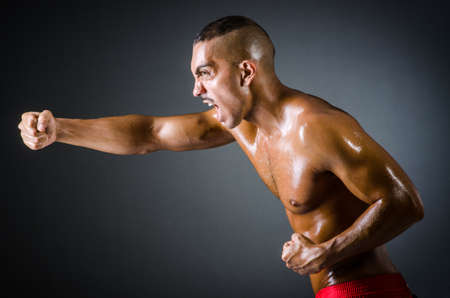 Muscular boxer in dark studio photo