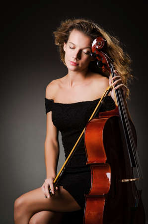 Woman performer with cello  in studio photo