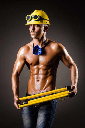 protective goggles: Construction worker in dark studio Stock Photo