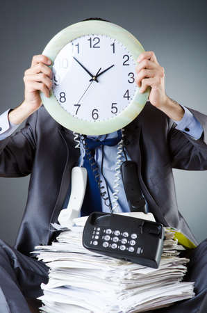 Man with clock and pile of papers Stock Photo - 18014430