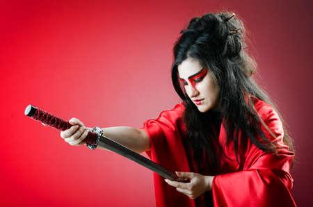 Female sword warriod in dark studio photo