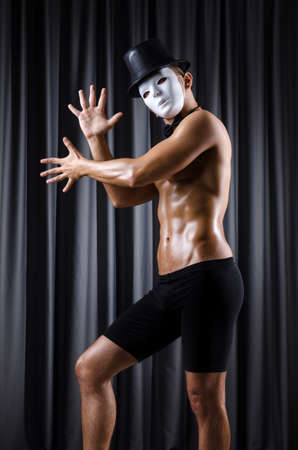 Muscular actor with mask against curtain Stock Photo - 18037179