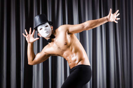 Muscular actor with mask against curtain Stock Photo - 18037222