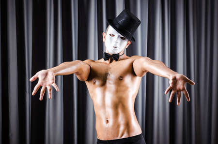 Muscular actor with mask against curtain Stock Photo - 18037697