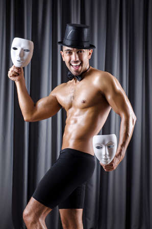 Muscular actor with mask against curtain Stock Photo - 18037527