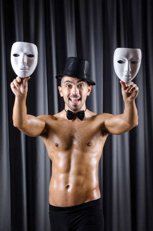 Muscular actor with mask against curtain Stock Photo - 18037112