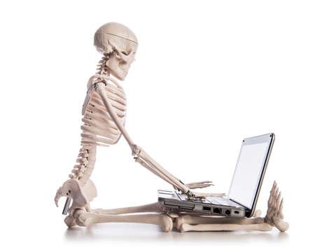 dreadful: Skeleton working on laptop Stock Photo
