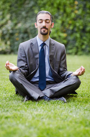 Young businessman meditating in the garden photo