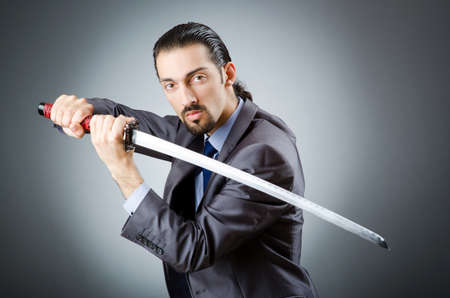 Angry businessman with sword in dark room photo